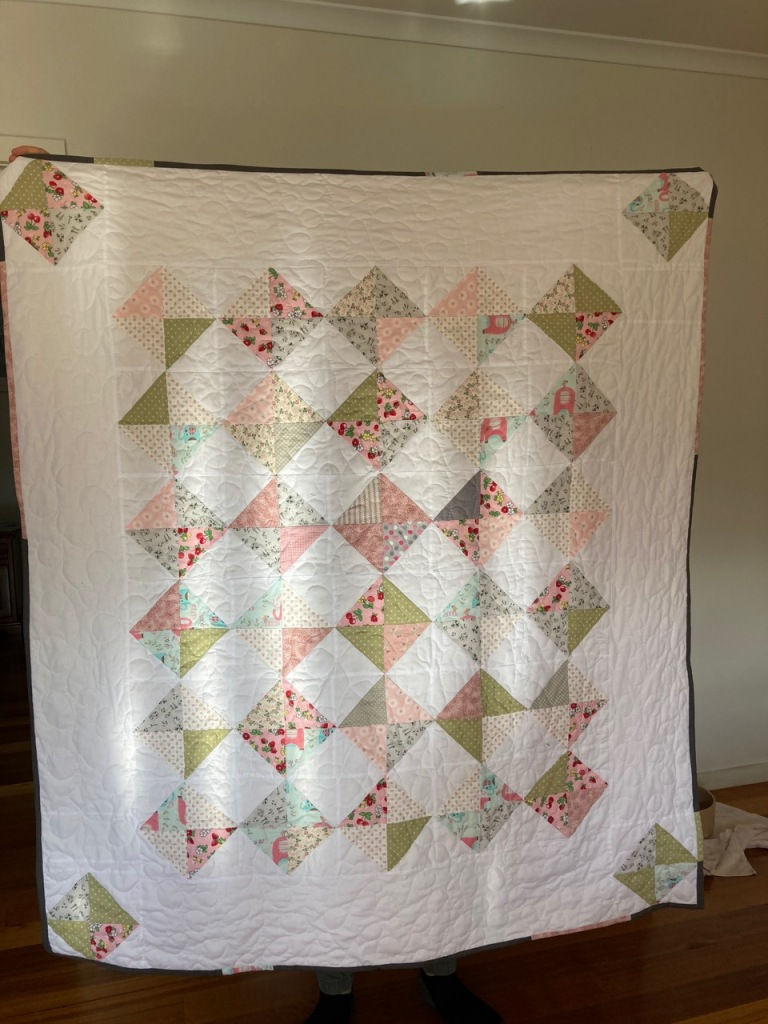 Photo of diamond blocked quilt in pinks, blues and sage green.